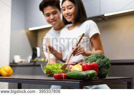 Asian Couple Cooking Together In Kitchen, Focus On Vegetables Lying On Table. Japanese Girlfriend An