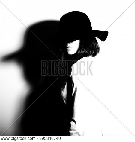 Mysterious fashion young woman in black hat and white shirt, copy space where can the advertising message be written, black and white