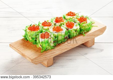 Sushi Roll With Caviar And Chuka Seaweed On Wooden Board.