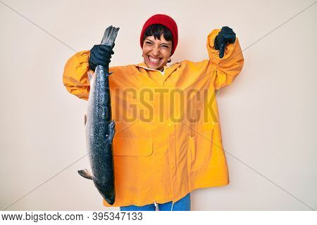 Beautiful brunettte fisher woman wearing raincoat holding fresh salmon with angry face, negative sign showing dislike with thumbs down, rejection concept