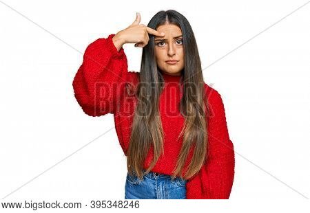 Beautiful hispanic woman wearing casual clothes pointing unhappy to pimple on forehead, ugly infection of blackhead. acne and skin problem