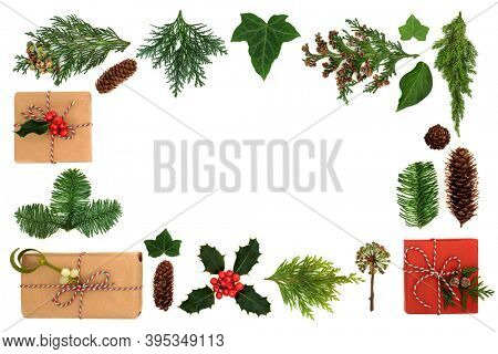 Christmas border with eco friendly gift wrapped boxes & winter greenery with holly, firs, ivy & pine cones on white background. Xmas green recycling concept. Flat lay, top view, copy space.