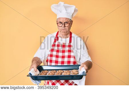 Senior grey-haired man wearing baker uniform holding homemade cookies depressed and worry for distress, crying angry and afraid. sad expression.