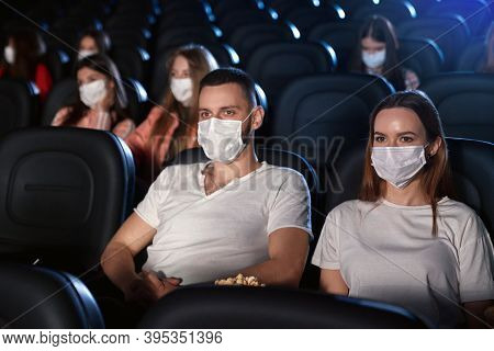 Young Man And Woman In Casual Outfits Enjoying Date During World Pandemic, Holding Popcorn. Selectiv
