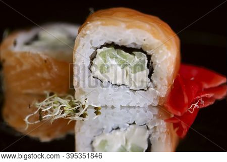Food. Rolls Philadelphia On A Black Background On A Mirror Surface. Japanese Rolls Close Up. Free Sp
