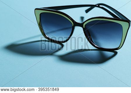 Sunglasses Close Up. The Shadow From The Glasses Falls On The Blue Surface. Horizontal, Free Space O
