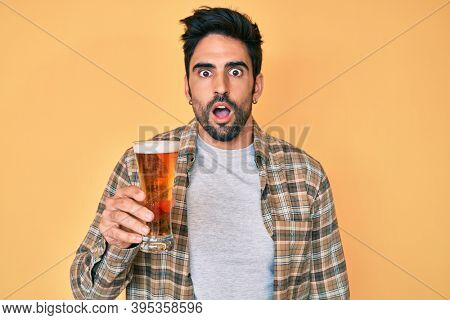Handsome hispanic man with beard drinking a pint of beer scared and amazed with open mouth for surprise, disbelief face