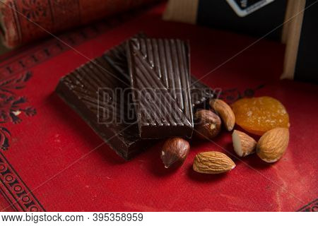 Close-up Of A Homemade Chocolate Bar With Raisins, Dried Apricot And Nuts On Red Book Background