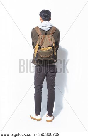 Back view full length portrait of young man in sweatshirts with jacket and black pants and brown backpack standing on white background