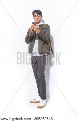 full length portrait of young man in sweatshirts with jacket and black pants and brown backpack , talking on mobile phone  standing on white background