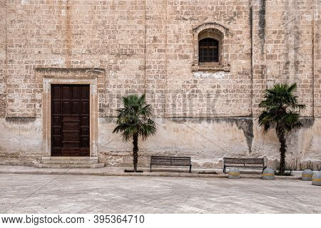 Church Stone Wall, Door And Window. Palm Trees And Benches. Monopoli, Italy.