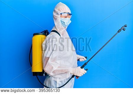 Covid specialist wearing decontamination protective suit and disinfectant spray, decontaminate and sanitize surface, standing over blue background