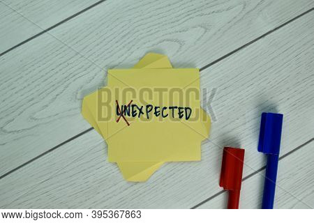 Unexpected Or Expected Write On A Book Isolated On Wooden Table.
