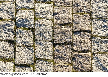 Old Cobblestone Background With Grass, Texture Of Stone Paving Stones.