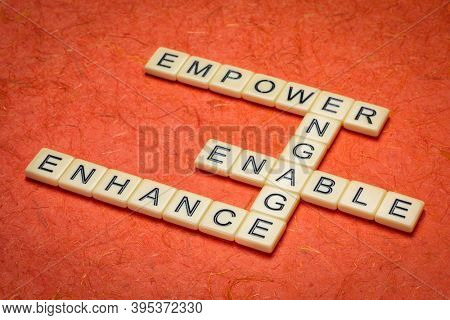 motivational leadership, coaching business or personal development concept - empower, enhance, enable and engage crossword in ivory letter tiles against textured handmade paper
