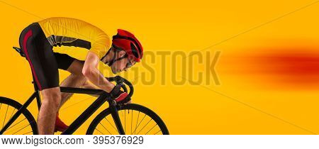 Man racing cyclist in motion on yellow background. Man in yellow cycling jersey.  Sports banner. Horizontal copy space background