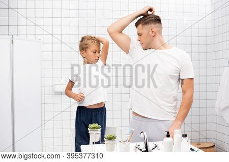 Father And Son Smelling Armpits While Standing Near Sink With Toiletries In Bathroom, Stock Image