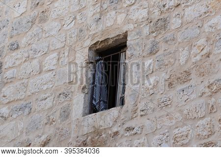 An Arabic Headscarf With A National Pattern Hangs On A Metal Lattice In A Building Window On The Via