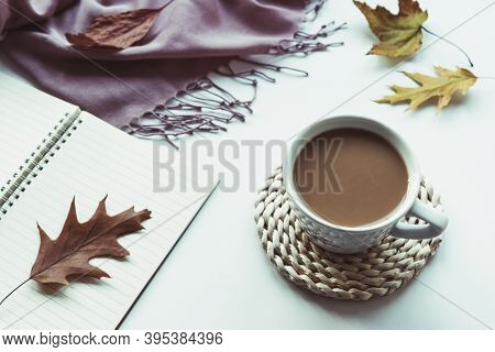 Autumn Flat Lay With Coffee Cup, Notepad, Fallen Leaves And Pink Shawl On White Background. Top View
