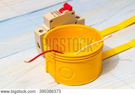 Yellow Electrical Junction Box And Circuit Breaker With Wires On Blue Boards