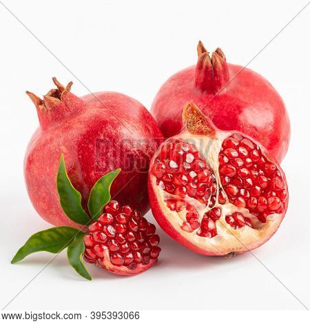 Healthy ripe pomegranate fruit and half of a juicy pomegranate with leaves on a white background.