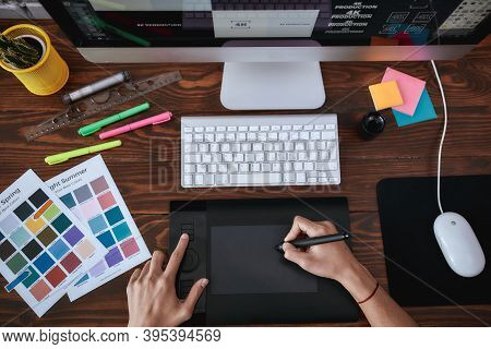 Top View Of A Designer Using Graphic Tablet And Working With Computer While Sitting At His Workplace
