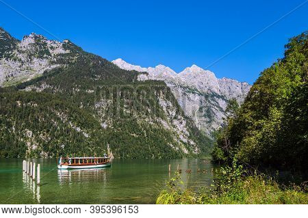 Lake Koenigssee With Rocks And Excursion Boat In The Berchtesgaden Alps, Germany.