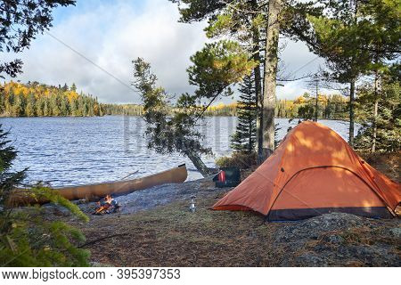 Campsite With Orange Tent On Northern Minnesota Lake At Sunrise During Autumn