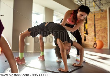 Full-length Shot Of Female Trainer Helping Boy While Kids Are Practising Yoga By Bending Backwards O
