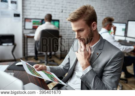 Young Trader Sitting By Desk And Looking Seriously At Analytical Reports While Working In The Office