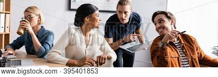 African American Woman Looking At Co-workers While Sitting At Desk Near Colleague Drinking Coffee In