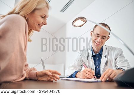 Smiling Doctor Writing In The Presence Of His Patient