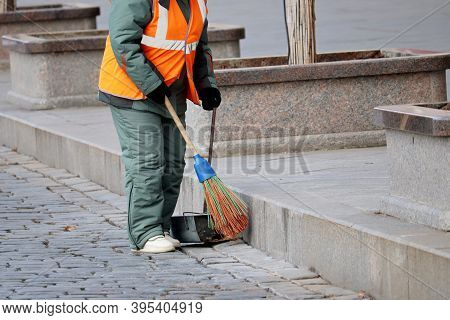 Street Cleaning, Female Municipal Worker In Uniform Sweeping The Sidewalk With A Broom. Janitor In W