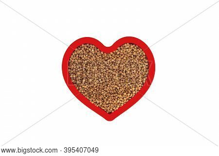 Brown Buckwheat Groats In Heart Shape Red Frame Isolated On White Background