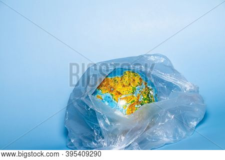 The Concept Of Ecology. Globe In Plastic Wrap On A Blue Background. Plastic Waste Environmental Poll