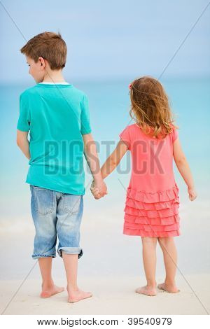 Back view of two small kids at exotic beach