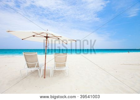 Two chairs under umbrella on a beautiful tropical beach in Turks and Caicos