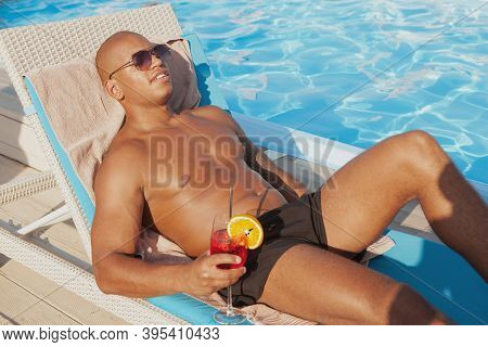 Attractive Relaxed African Man Enjoying Sunbathing, Having A Drink At The Poolside. Handsome Athleti