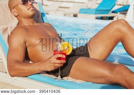 Cropped Shot Of A Muscular African Man Relaxing Near The Swimming Pool, Holding Cocktail, Copy Space