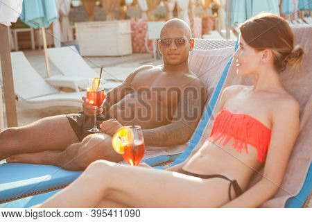 Young Woman Relaxing At The Beach With Her Handsome Boyfriend. Multiethnic Couple Resting At The Sea