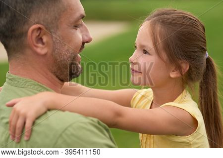 Close Up Of Joyful Little Girl Looking At Her Happy Dad, Hugging Him While Spending Time Together Ou