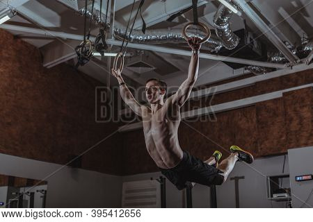 Low Angle Shot Of A Male  Athlete Exercising On Gymnastic Rings. Shirtless Strong Sportsman