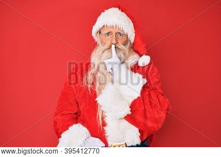 Old senior man with grey hair and long beard wearing traditional santa claus costume asking to be quiet with finger on lips. silence and secret concept.