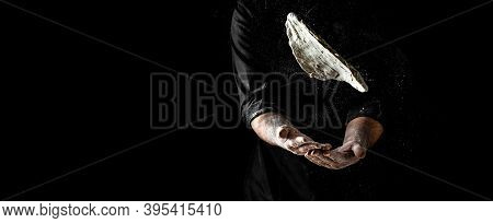 Pizza Cook's Hand With Dough, Powdery Flour Flying Into Air. Chef Hands With Flour In A Freeze Motio