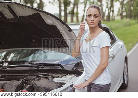 Young Beautiful Woman Looking Worried, Calling Roadside Assistance, Standing Near Her Car With An Op