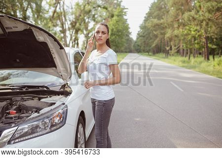 Beautiful Young Woman Calling For Help, Standing Near Her Broken Down Car On The Side Of The Road, C