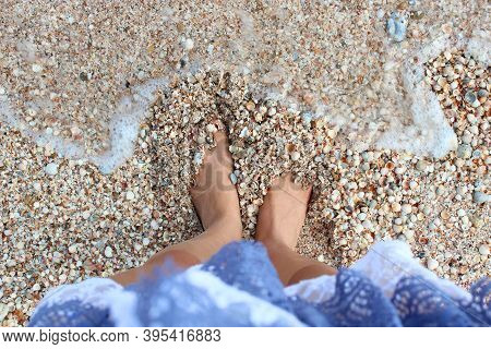 Girl In A Blue Dress Stands With Bare Feet On The Beach The Sea Washes Her Feet. The Sea Washes Wome