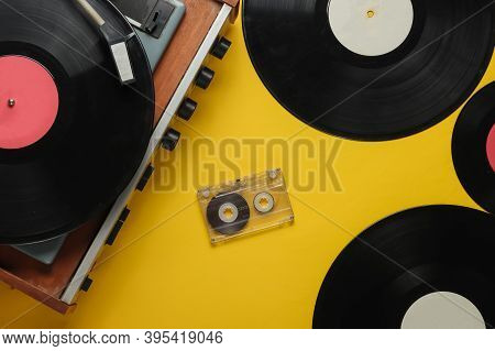 Old-fashioned Vinyl Player With Records And Audio Cassette On Yellow Background. Retro Media 70s. To