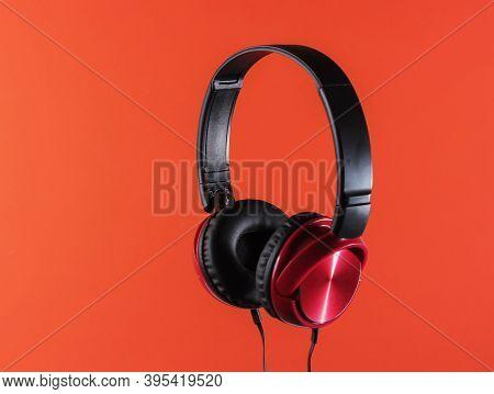 New Headphones With Cable. Minimalist Photo Of Earphones On Orange Background. Black Red Dj Headphon