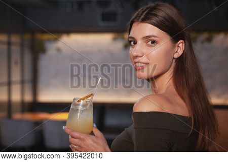 Close Up Of A Beautiful Young Woman Smiling Over Her Shoulder To The Camera, Enjoying A Drink At The